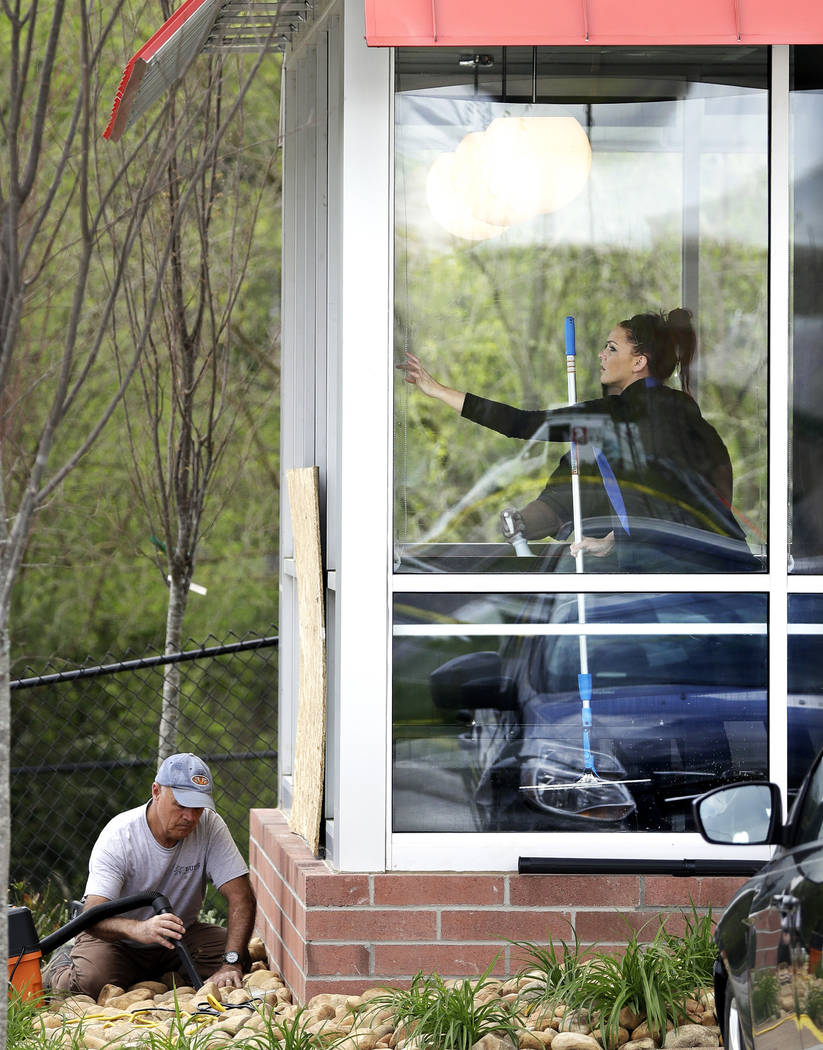 A worker vacuums debris from shattered glass as another worker cleans windows inside a Waffle House restaurant Monday, April 23, 2018, in Nashville, Tenn. A suspect police have identified as Travi ...