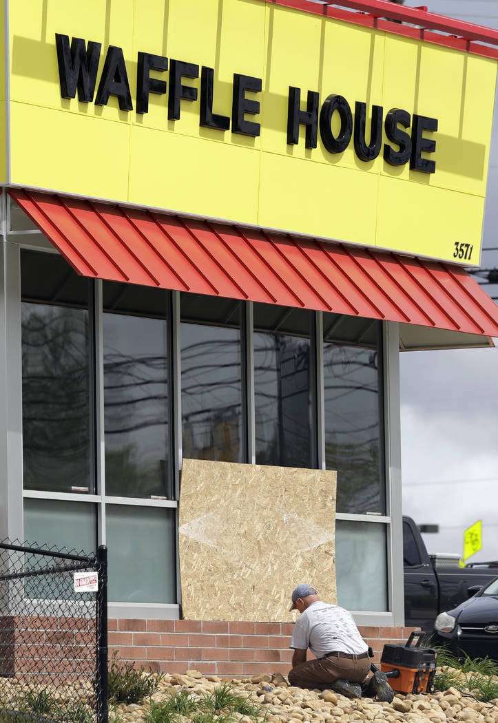 A worker vacuums up shattered glass outside a Waffle House restaurant Monday, April 23, 2018, in Nashville, Tenn. A suspect police have identified as Travis Reinking shot and killed at least four ...
