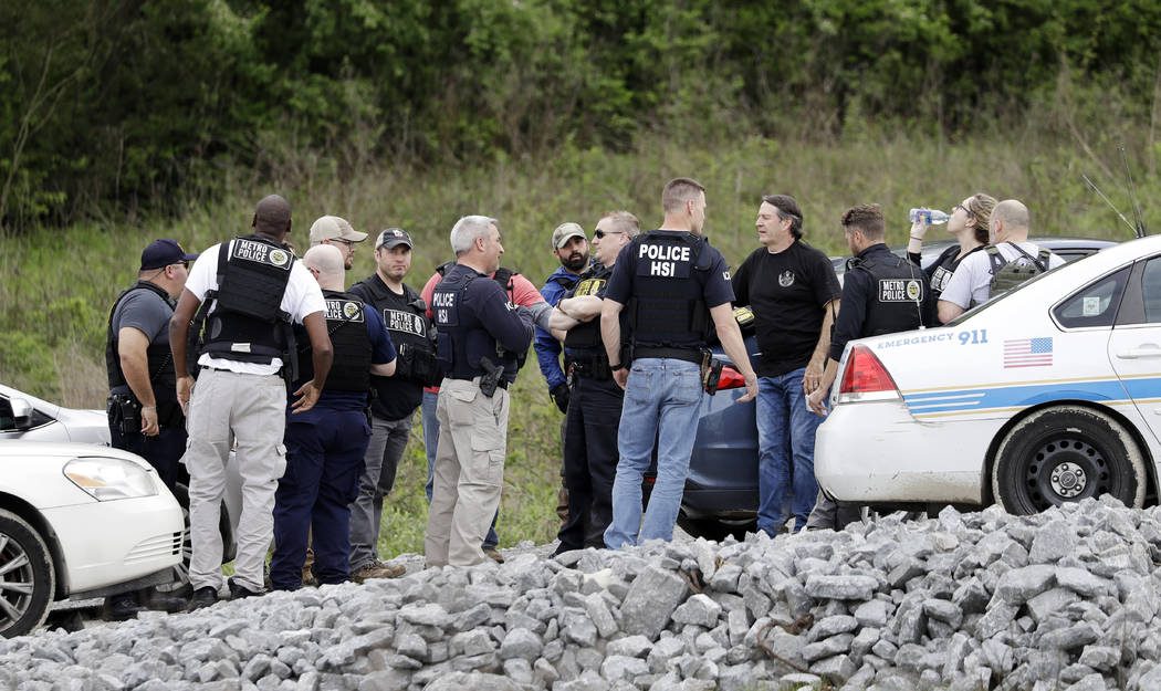 Police gather on a road along a wooded area where Waffle House shooting suspect Travis Reinking was captured Monday, April 23, 2018, in Nashville, Tenn. Police say Reinking shot and killed at leas ...