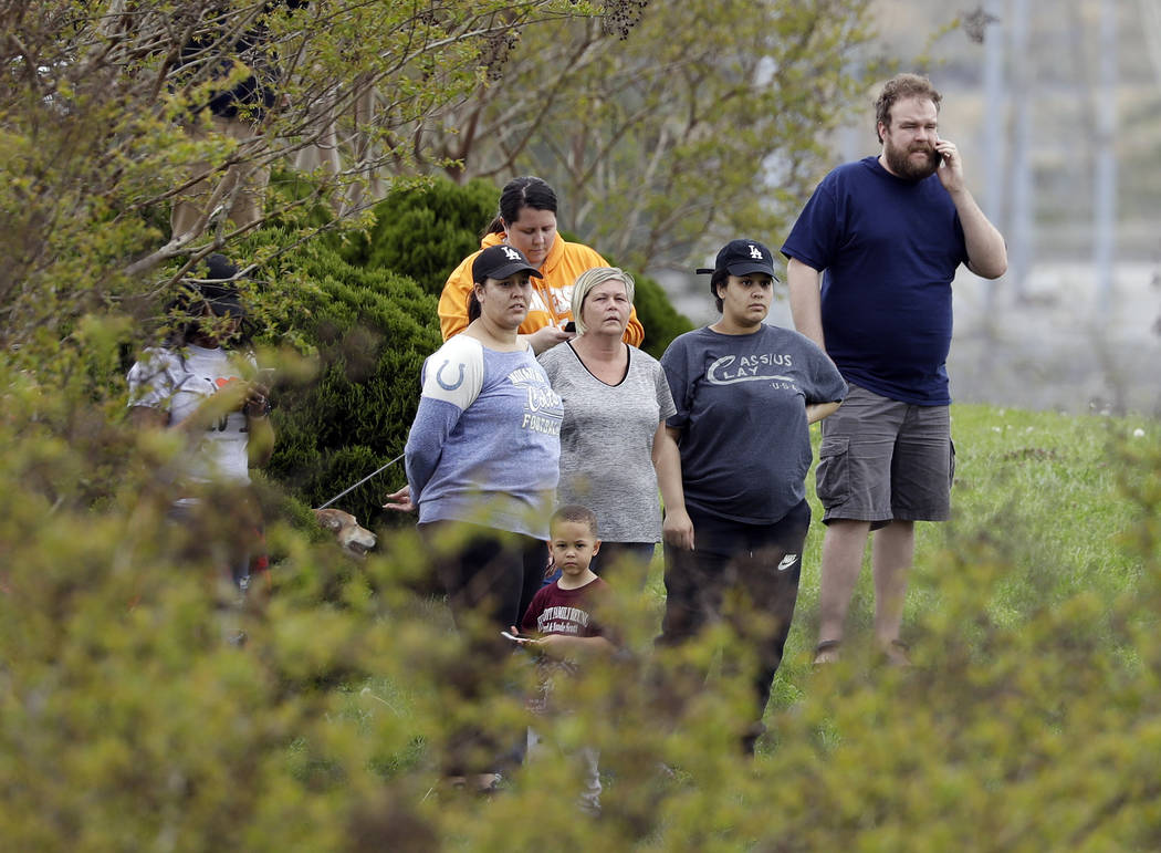 Residents of the apartment complex where Waffle House shooting suspect Travis Reinking lived watch as police work near the wooded area where Reinking was captured Monday, April 23, 2018, in Nashvi ...