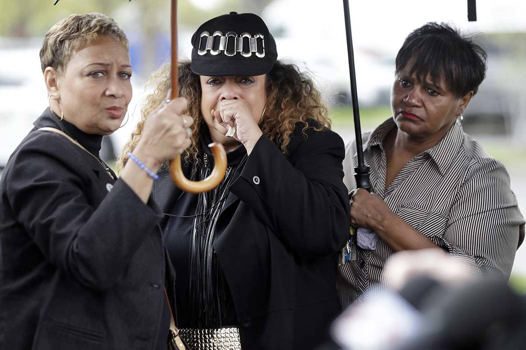 A woman, center, who would only be identified as the godmother of shooting victim DeEbony Groves, cries as she listens at a news conference regarding the capture of Travis Reinking Monday, April 2 ...