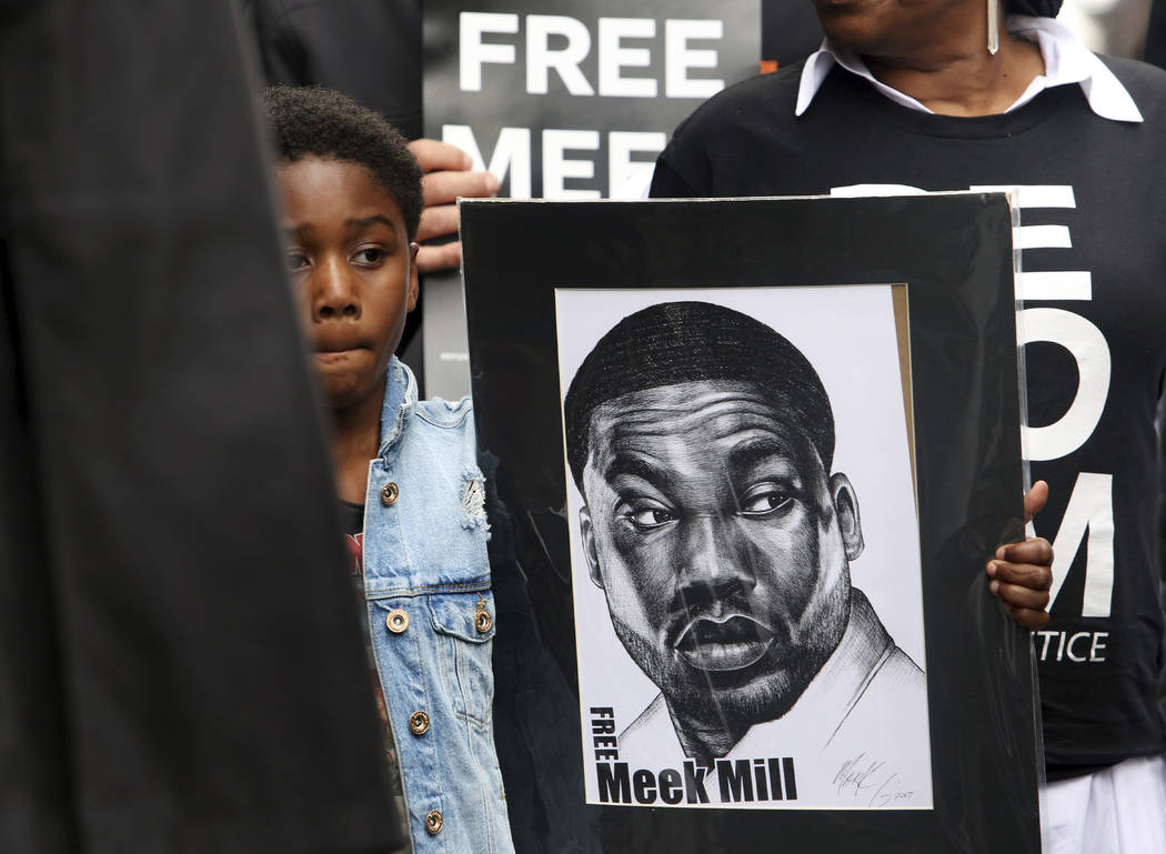 Rapper Meek Mill's son Papi holds a sign as protesters demonstrate in front of a courthouse during a hearing for Meek Mill, Monday April 16, 2018 in Philadelphia. (AP Photo/Jacqueline Larma)