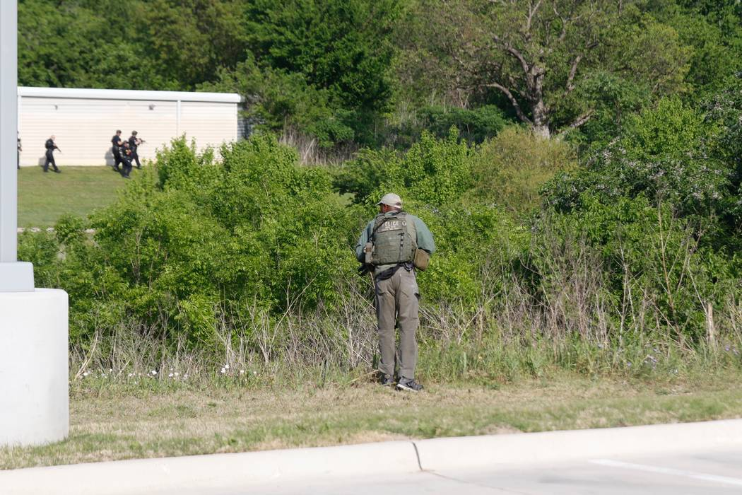 Dallas Police look for a suspect in the shooting of two police officers and a civilian Tuesday, April, 24,2018. Police are near ExtraSpace Storage, south of The Home Depot. Officer in the foregrou ...