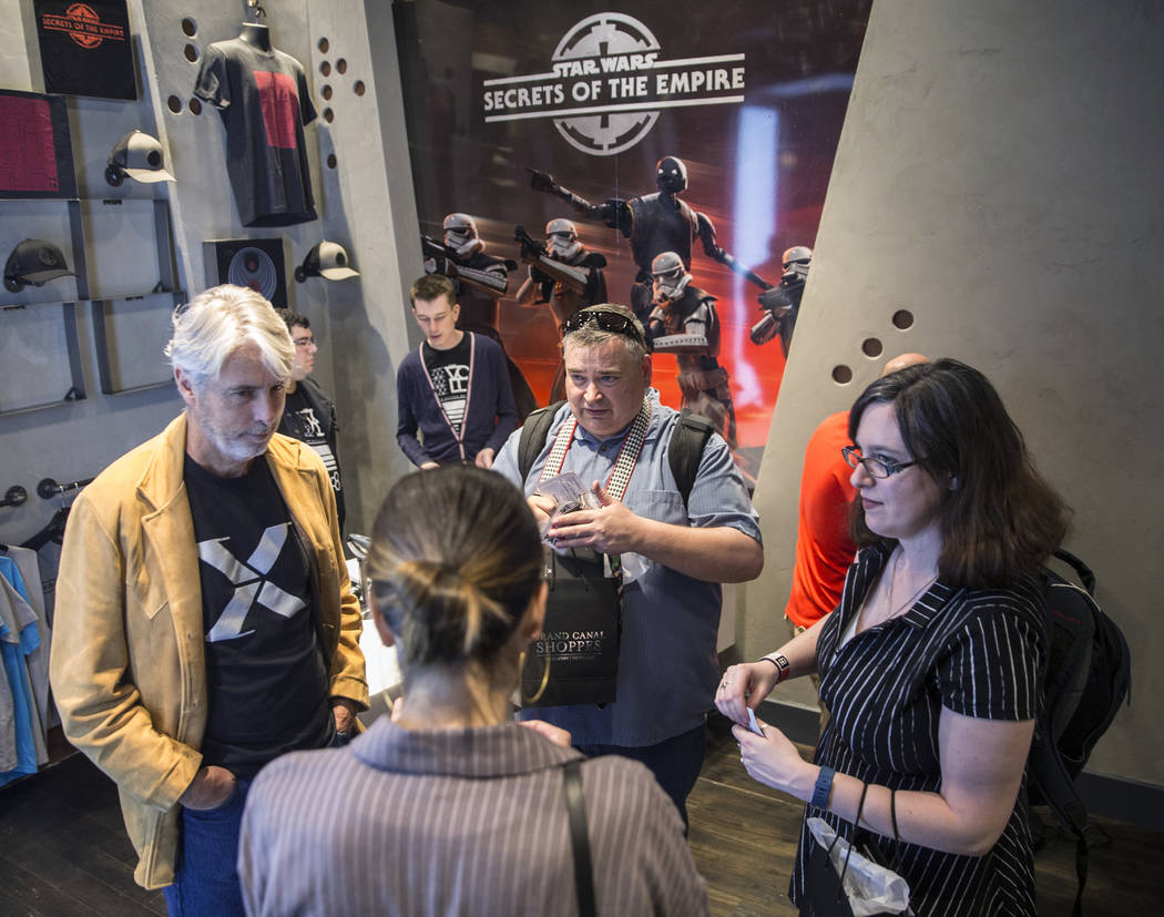 """Mark Miller, left, executive creative producer at ILMxLAB, Denzel Eslinger and Kaitlyn Booth discuss the new """"Star Wars: Secrets of the Empire"""" VR experience at the Grand Canal Shoppes o ..."""