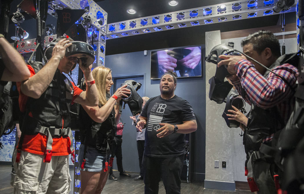 """Guest services agent Faafetai Nunu, middle, preps guests for the new """"Star Wars: Secrets of the Empire"""" VR experience at the Grand Canal Shoppes on Tuesday, April 24, 2018, in Las Vegas. ..."""