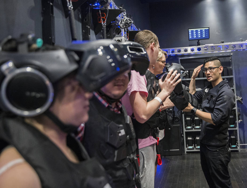 """Team leader Gabriel Urena, right, preps guests for the new """"Star Wars: Secrets of the Empire"""" VR experience at the Grand Canal Shoppes on Tuesday, April 24, 2018, in Las Vegas. Benjamin ..."""