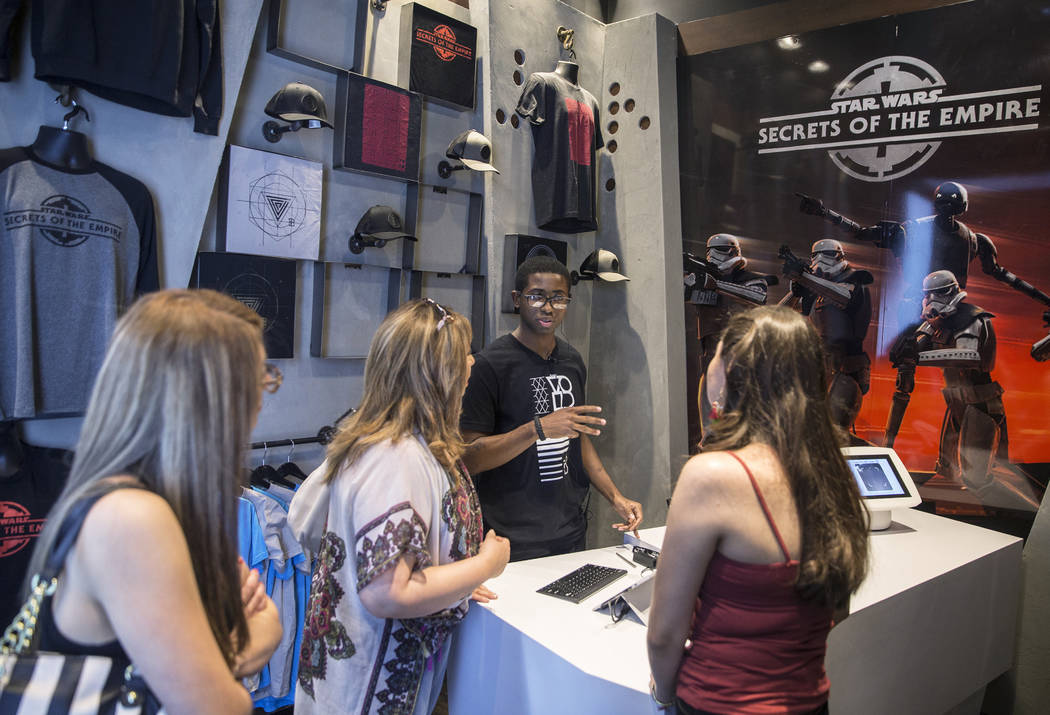"""Guest services agent Shanon Demoulin, third from left, signs people into the new """"Star Wars: Secrets of the Empire"""" VR experience at the Grand Canal Shoppes on Tuesday, April 24, 2018, i ..."""