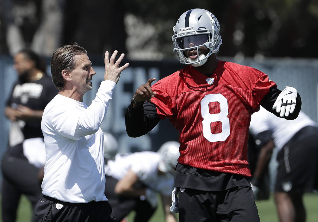 Oakland Raiders offensive coordinator Greg Olson, left, talks with quarterback Josh Johnson at the NFL football team's football facility in Alameda, Calif., Tuesday, April 24, 2018. (AP Photo/Jeff ...