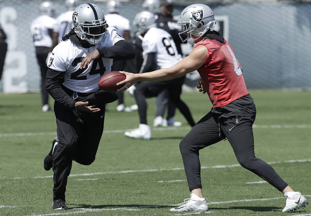 Oakland Raiders running back Marshawn Lynch, left, takes a handoff from quarterback Derek Carr at the NFL football team's facility in Alameda, Calif., Tuesday, April 24, 2018. (AP Photo/Jeff Chiu)