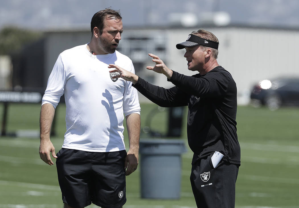 Oakland Raiders head coach Jon Gruden, right, talks with tight ends coach Frank Smith at the team's football facility in Alameda, Calif., Tuesday, April 24, 2018. (AP Photo/Jeff Chiu)