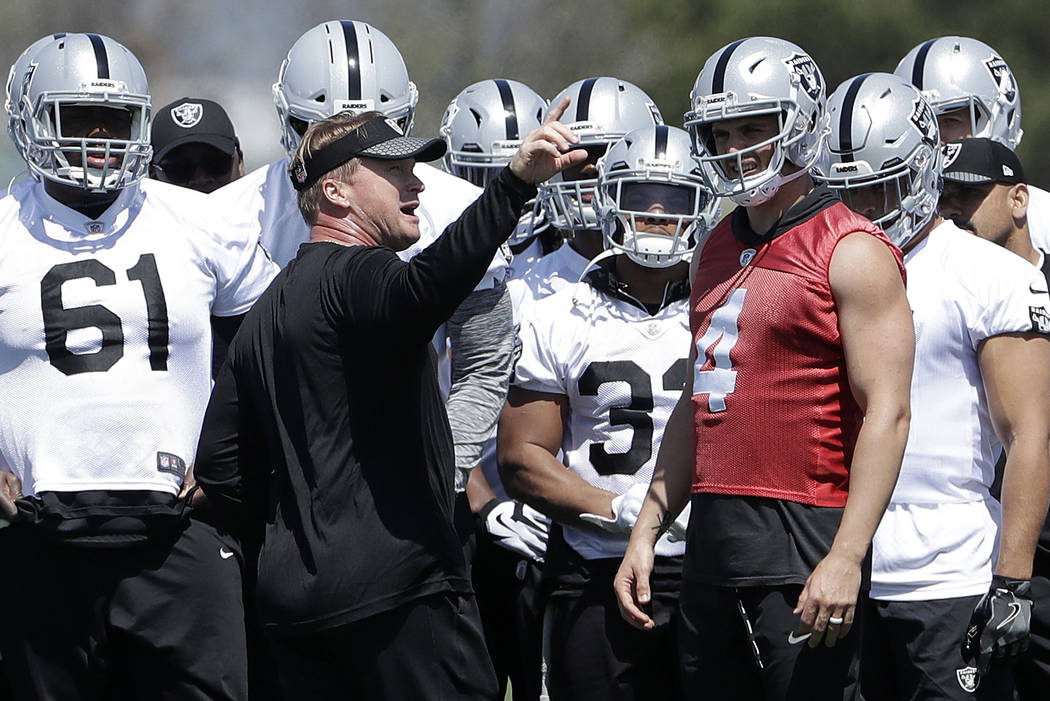 Oakland Raiders coach Jon Gruden, center left, talks with quarterback Derek Carr (4) and offensive players at the NFL football team's facility in Alameda, Calif., Tuesday, April 24, 2018. (AP Phot ...