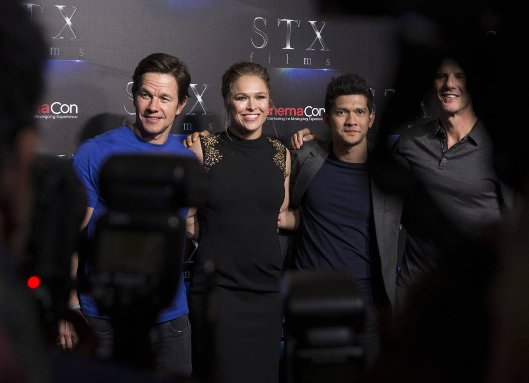 Mark Wahlberg, left, Ronda Rousey, Iko Uwais and Peter Berg take photos during the STXfilms red carpet event on the second night of CinemaCon on Tuesday, April 24, 2018, at Caesars Palace hotel-ca ...