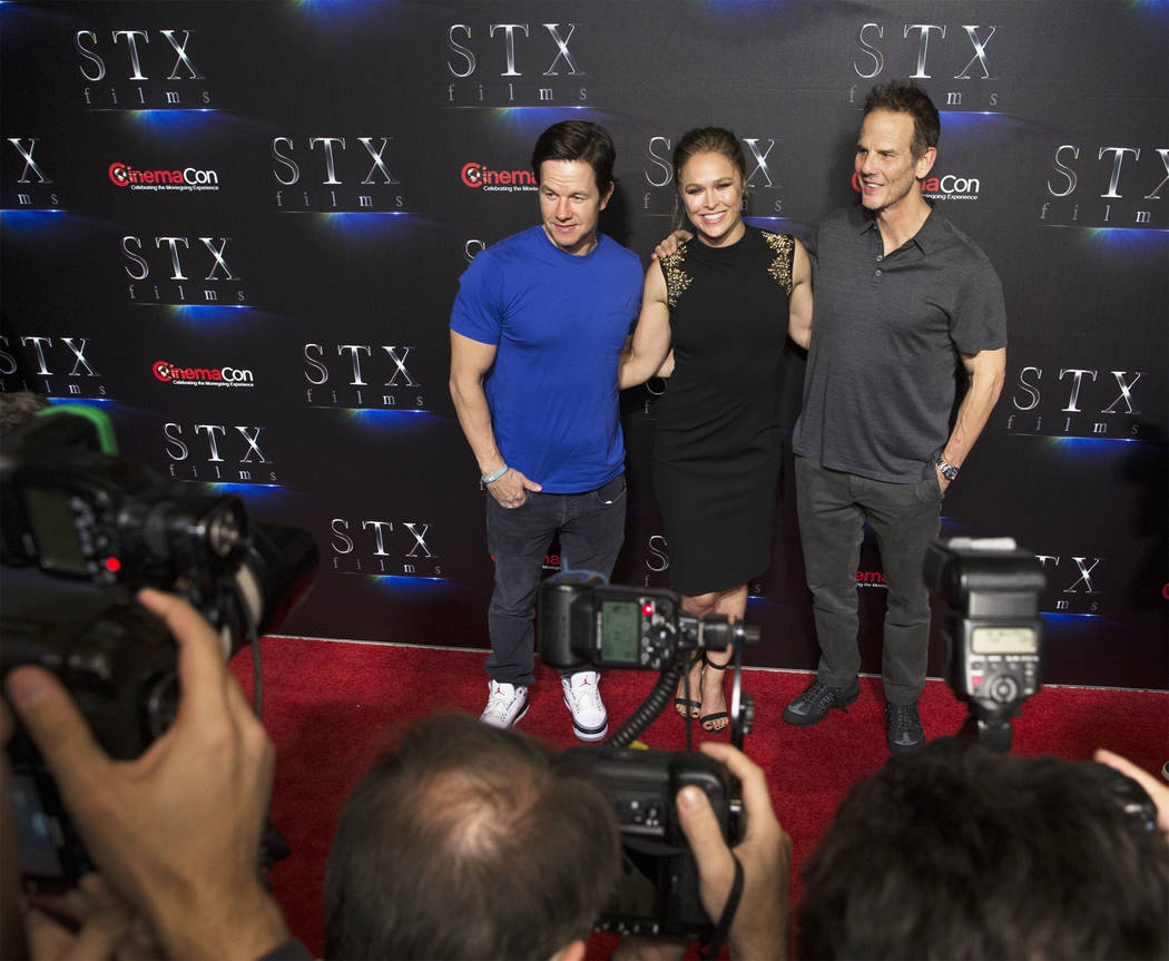 Mark Wahlberg, left, Ronda Rousey and Peter Berg take photos during the STXfilms red carpet event on the second night of CinemaCon on Tuesday, April 24, 2018, at Caesars Palace hotel-casino, in La ...