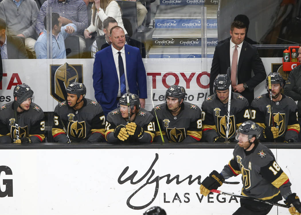 Golden Knights head coach Gerard Gallant, in blue, watches the action as his team plays the Vancouver Canucks during the second period of an NHL hockey game at T-Mobile Arena in Las Vegas on Tuesd ...