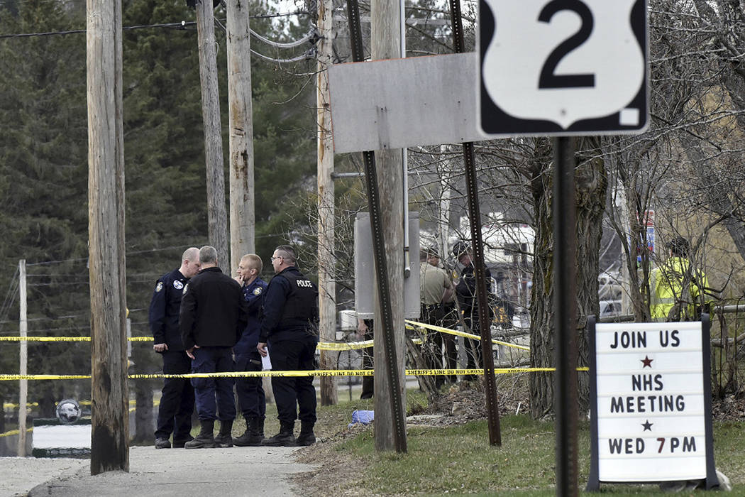 Police officers stand along U.S. Route 2 on Wednesday, April 25, 2018, in Norridgewock, Maine, after Somerset County Sheriff's Deputy Eugene Cole was killed there overnight. A Maine man killed the ...