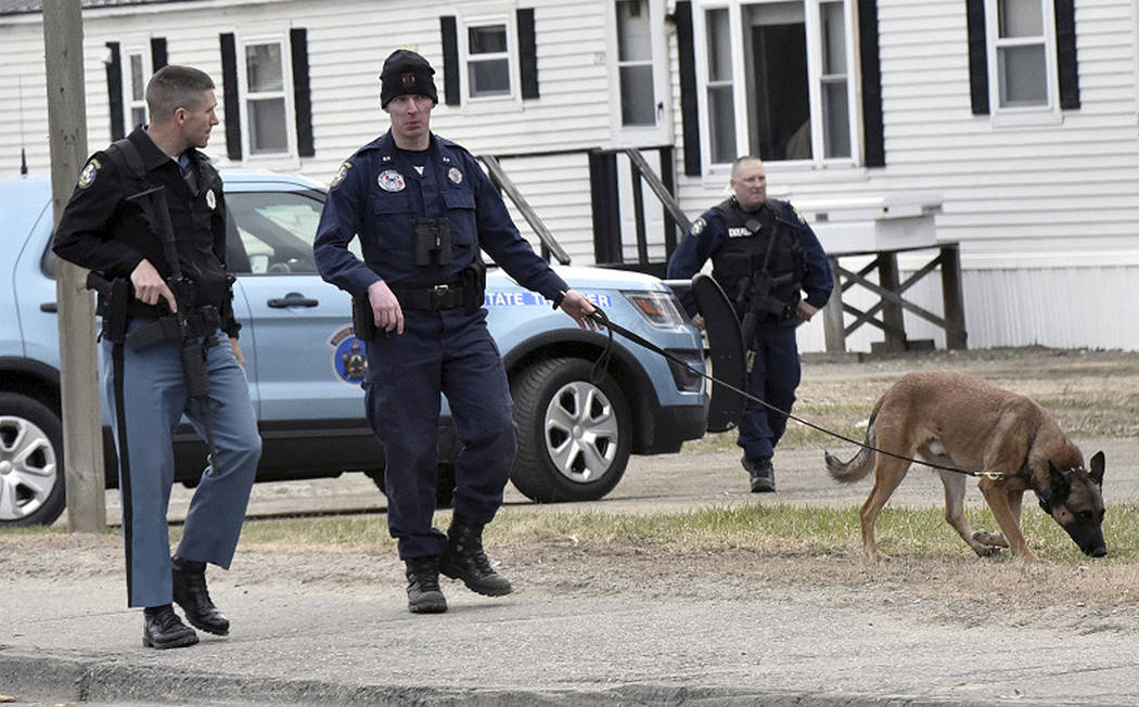 Police spread out to search on North Street in Skowhegan, Maine, on Wednesday, April 25, 2018, after Somerset County Sheriff's Deputy Eugene Cole was killed overnight in nearby Norridgewock, Maine ...