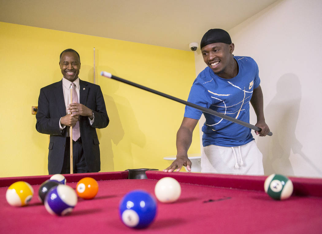 Ben Carson, left, Secretary of Housing and Urban Development, plays pool with resident Terrance McCoy during a tour of Shannon West Center for Homeless Youth on Wednesday, April 25, 2018, in Las V ...