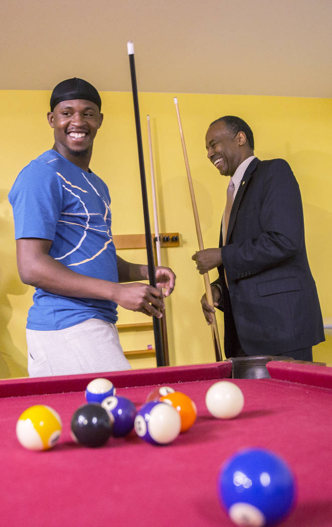 Ben Carson, right, Secretary of Housing and Urban Development, plays pool with resident Terrance McCoy during a tour of Shannon West Center for Homeless Youth on Wednesday, April 25, 2018, in Las ...