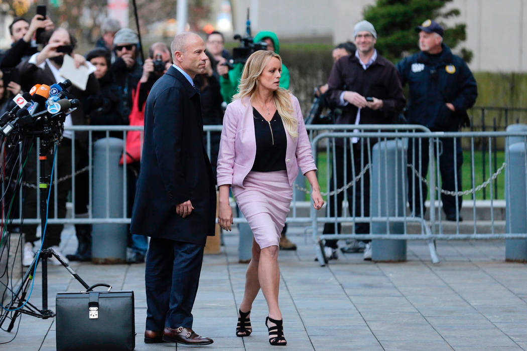 FILE - In this April 16, 2018, file photo, porn actress Stormy Daniels, accompanied by her attorney, Michael Avenatti, left, leaves federal court, in New York. A federal judge is set to hear argum ...