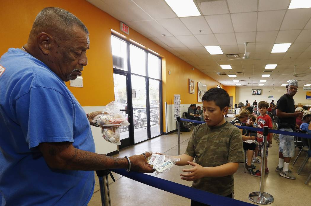 Volunteer Monroy Martinez, left, hands out a free to-go lunch to a boy at the St. Mary's Food Bank Alliance due to the Arizona teachers strike and closure of schools Thursday, April 26, 2018, in P ...