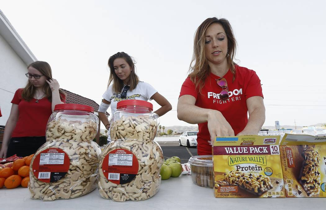 Jenn Gray, right, Ciara Schmalfeld, center, and Jessica Amstutz, left, help set up a special food table at the South Phoenix Missionary Baptist Church for kids affected by the Arizona teacher stri ...