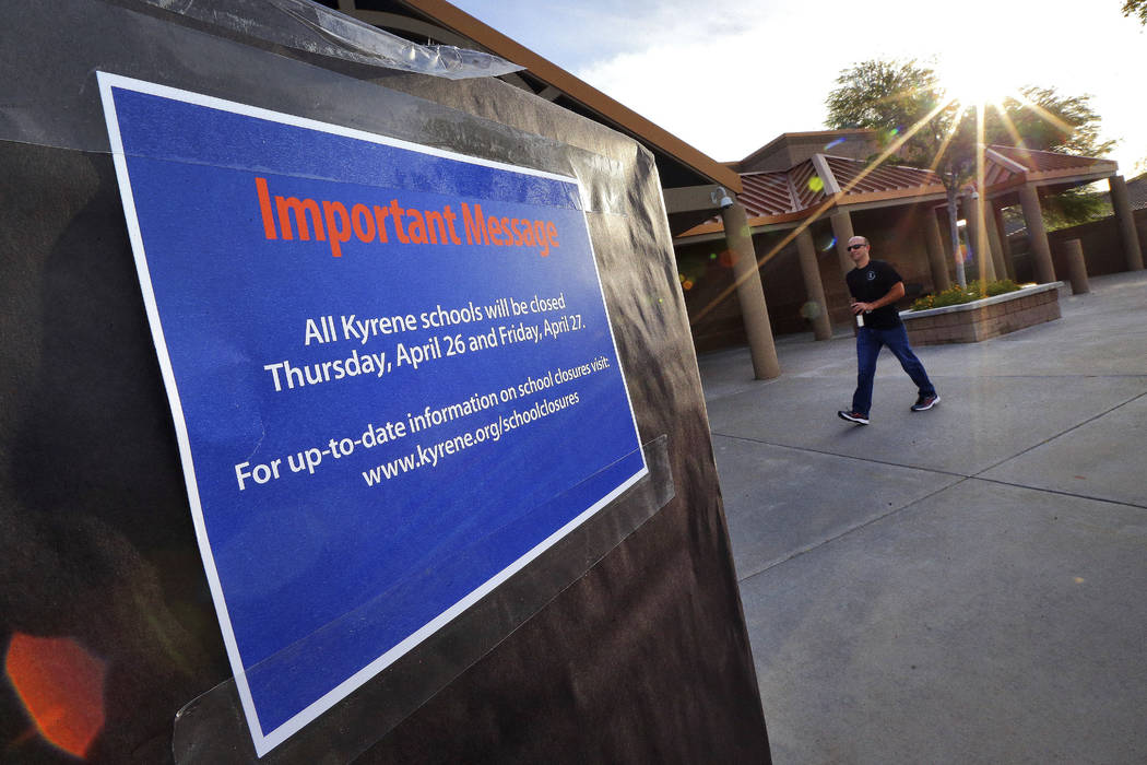 The sun rises over Kyrene De Las Lomas Elementary School, Thursday, April 26, 2018, in Phoenix, as a teacher arrives. Teachers in Arizona and Colorado walked out of their classes today over low sa ...