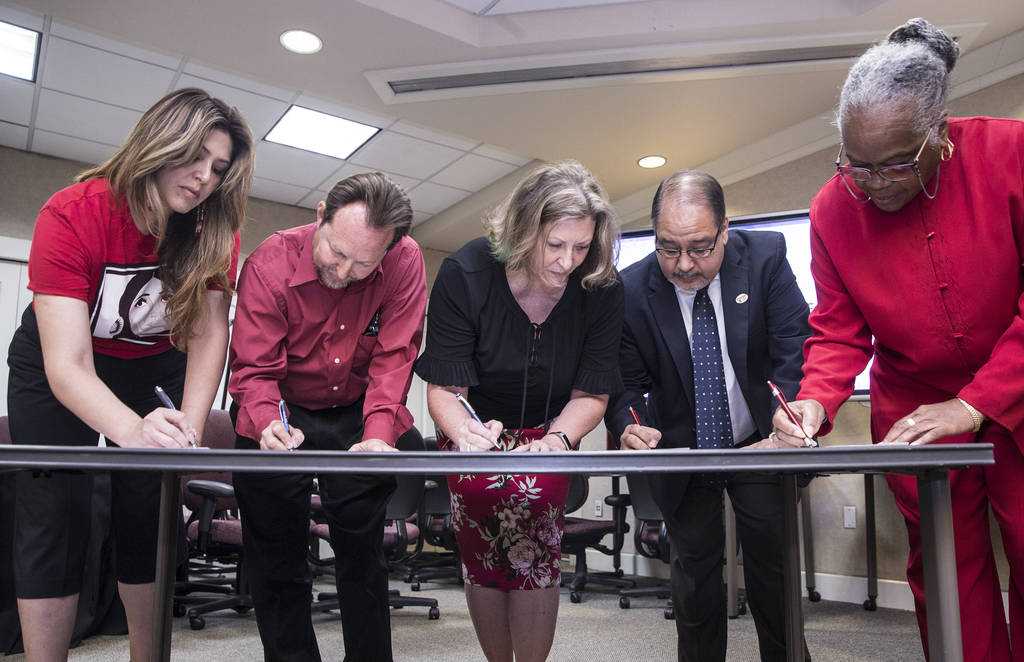 Mercedes Krause, left, Chet Miller, Carmen Andrews, Ruben Murillo and Patricia Stevens sign paperwork officially creating a new teachers union - the National Education Association-Southern Nevada ...