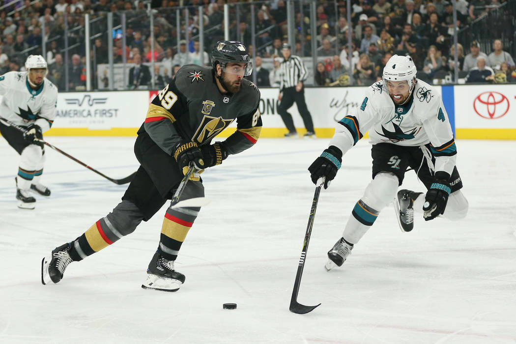 Vegas Golden Knights right wing Alex Tuch (89) and San Jose Sharks defenseman Brenden Dillon (4) go for the puck during the first period in Game 1 of an NHL hockey second-round playoff series at T ...