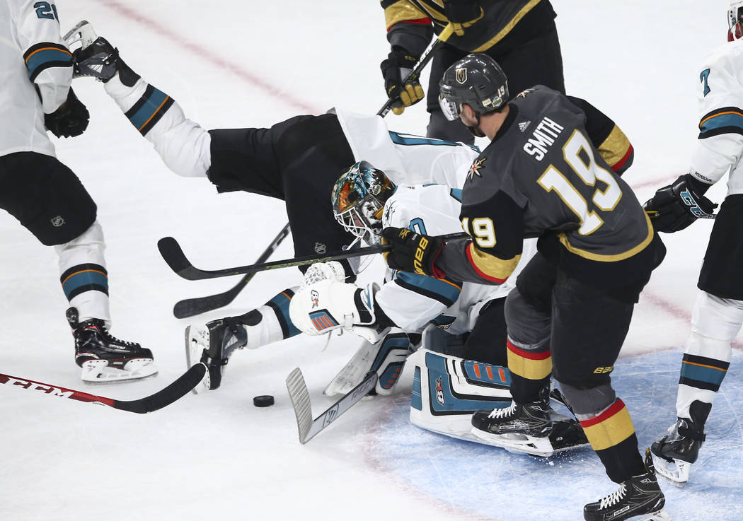 San Jose Sharks center Chris Tierney, center left, gets tripped up as San Jose Sharks goaltender Aaron Dell (30) goes for the puck while Golden Knights right wing Reilly Smith (19) looks on during ...