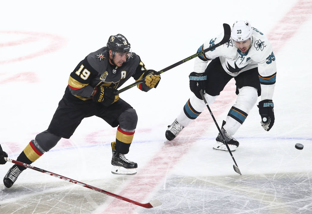 Golden Knights right wing Reilly Smith (19) and San Jose Sharks center Logan Couture (39) watch the puck pass by during the second period of Game 1 of an NHL hockey second-round playoff series at ...