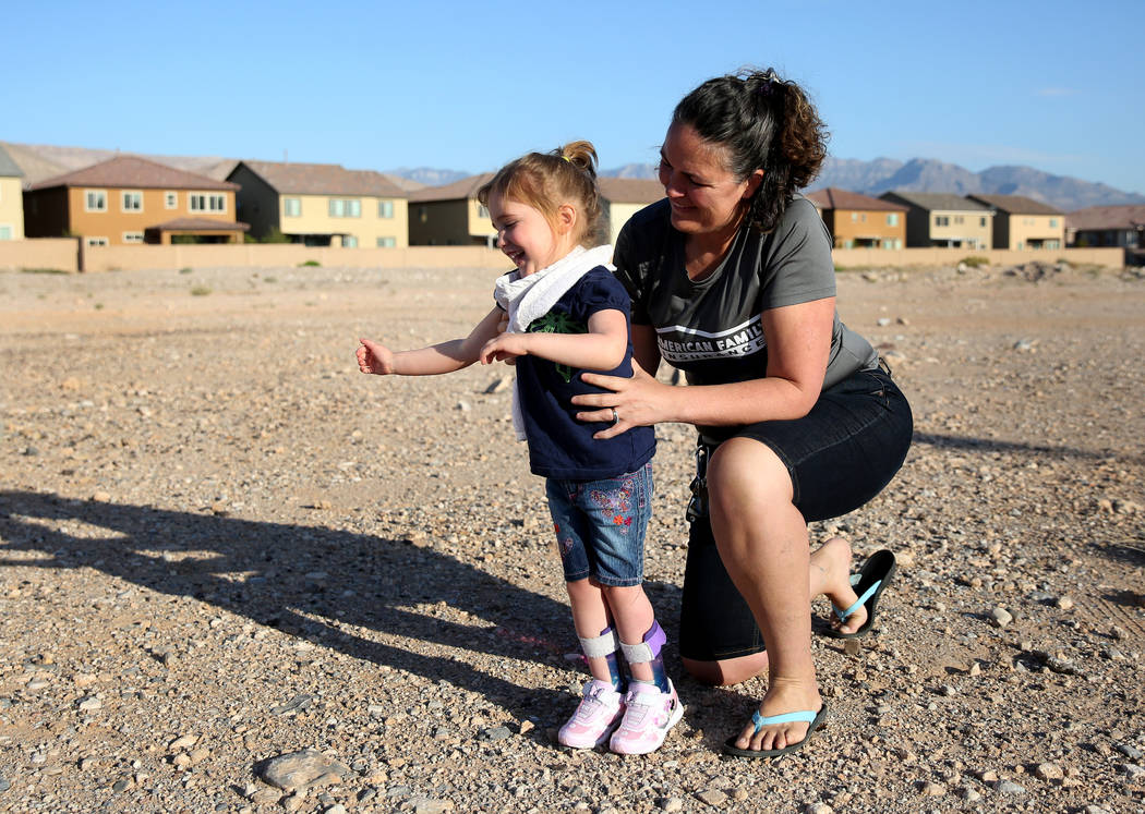 Mindy Winslow holds as her daughter Lexi's, 4, tries to walk after a hot air balloon ride on Friday, April 27, 2018, in Las Vegas. Local American Family Insurance agents are holding a fundraiser ...