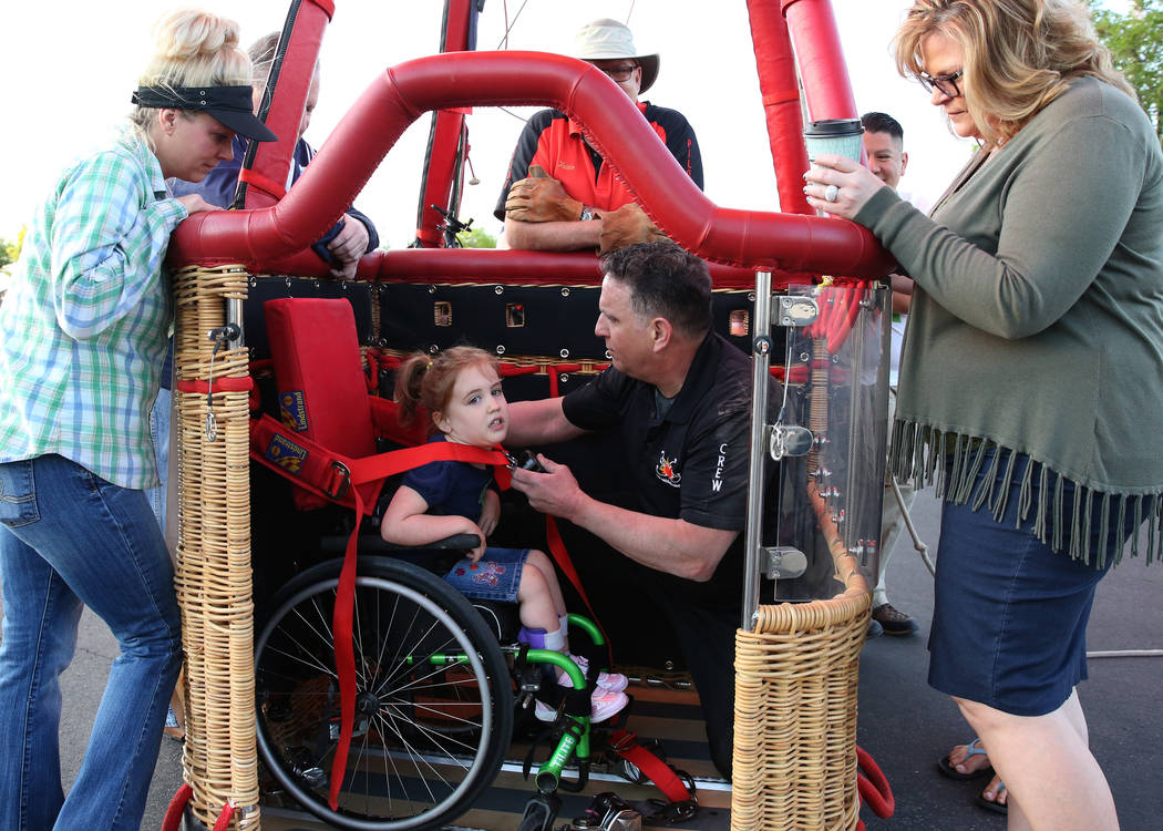 Tom Briones, chief crew at Love is in the Air Ballooning, secures Lexi Winslow's, 4, wheelchair as they prepare to take a hot air ballon ride on Friday, April 27, 2018, in Las Vegas. Local America ...