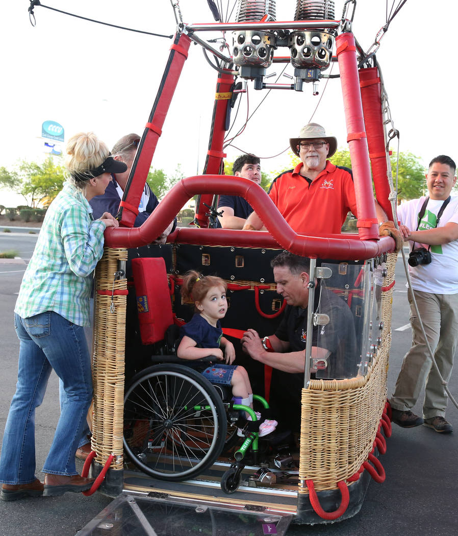 Tom Briones, chief crew at Love is in the Air Ballooning, secures Lexi Winslow's, 4, wheelchair as Kevin Cloney, center, chief pilot, looks on as they prepare to take a hot air ballon ride on Frid ...