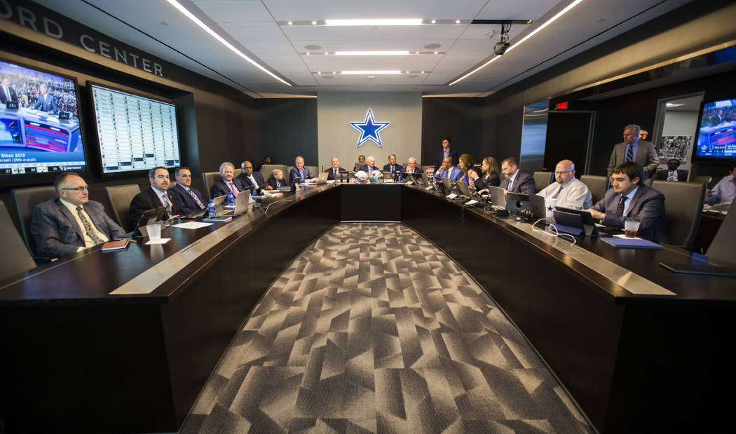 Dallas Cowboys Owner Jerry Jones, center, coach Jason Garrett, center left, CEO and Executive Vice President Stephen Jones, center right, and other Cowboys executives wait to make their first-roun ...
