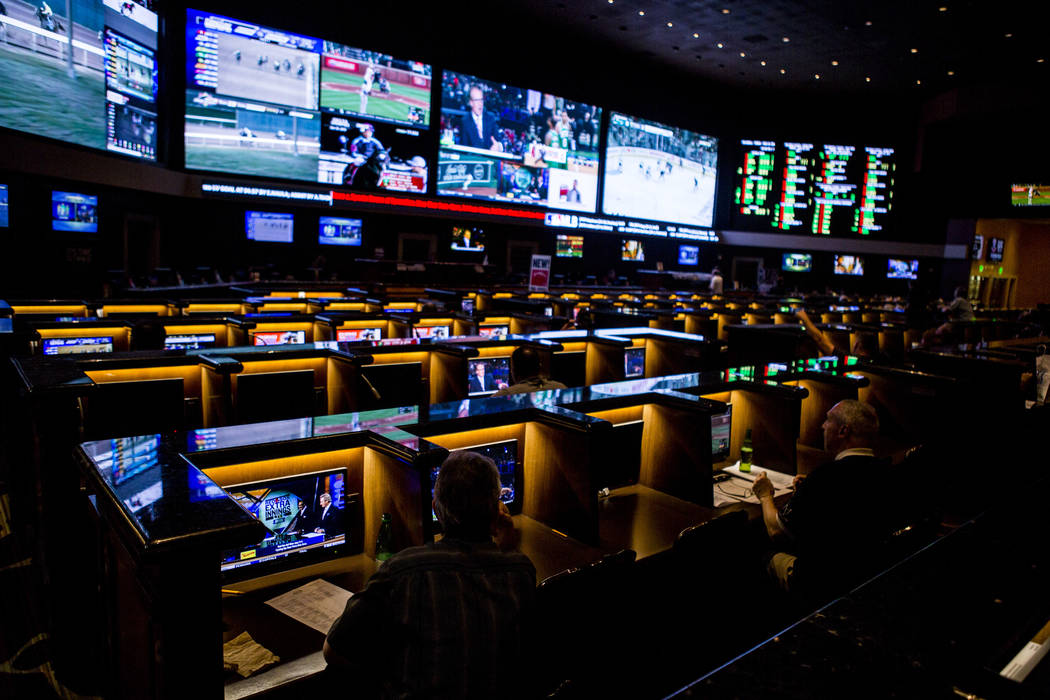 Sports betters watch games on individual screens as the the Golden Knights play the San Jose Sharks during the second round of the NHL playoffs at the Green Valley Ranch sports book in Henderson o ...