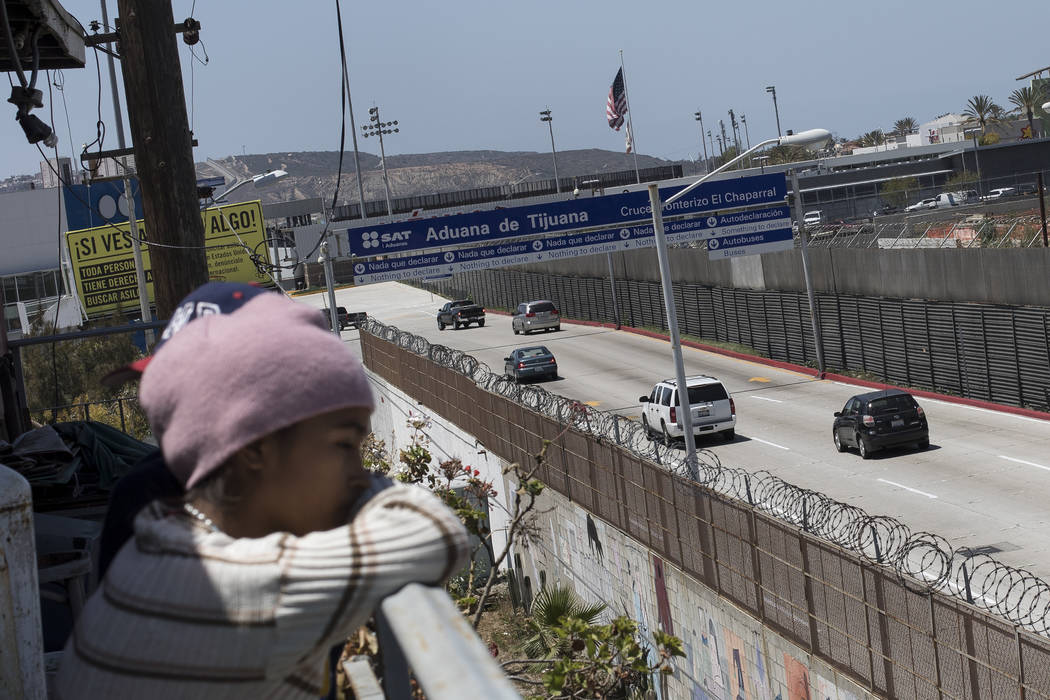 A migrant child from Honduras looks across the US-Mexico Border from Tijuana, Mexico, Friday, April 27, 2018. Close to 200 migrants from Central America, mostly from Honduras, arrived in Tijuana s ...