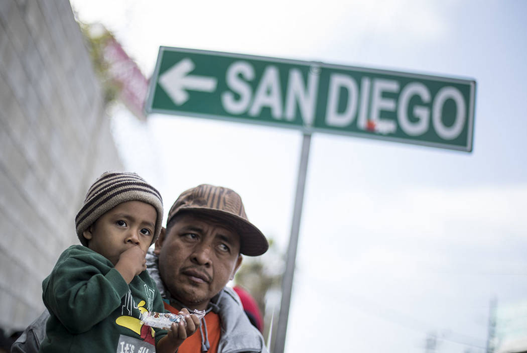 A father and his son await tutorship by immigration lawyers in Tijuana, Mexico, Friday, April 27, 2018. Close to to 200 migrants from Central America, mostly from Honduras, arrived in Tijuana seek ...