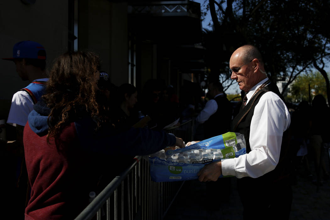 """Volunteer usher Larry LeBlanc hands out water while folks wait in line to get tickets to """"Hamilton"""" at The Smith Center in Las Vegas on Saturday, April 28, 2018. Andrea Cornejo Las Vegas ..."""