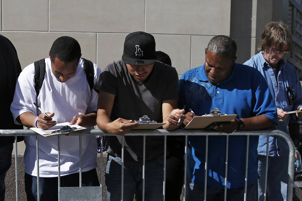 """From left, Mani Cockrell, 25, Alan Alavez, 25 and Lee Horton fill out paperwork while they wait in line for """"Hamilton"""" tickets at The Smith Center in Las Vegas on Saturday, April 28, 201 ..."""