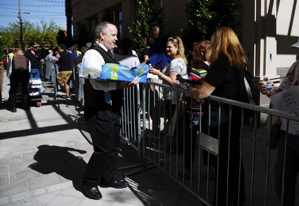 """Mark Sullivan, a volunteer usher, hands out water to folks waiting in line for """"Hamilton"""" tickets at The Smith Center in Las Vegas on Saturday, April 28, 2018. Andrea Cornejo Las Vegas R ..."""