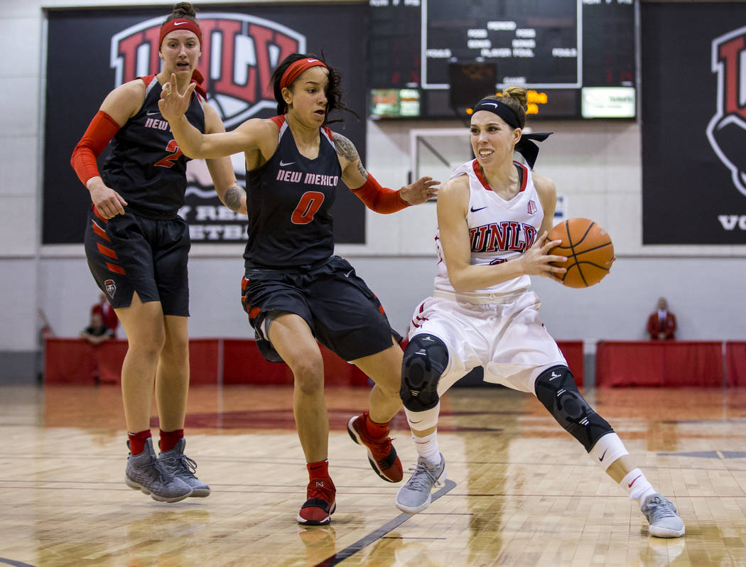 UNLV Rebels guard Brooke Johnson (2) takes the ball around New Mexico Lobos guard Cherise Beynon (0) and New Mexico Lobos guard Tesha Buck (2) at Cox Pavilion in Las Vegas on Saturday, Feb. 24, 20 ...
