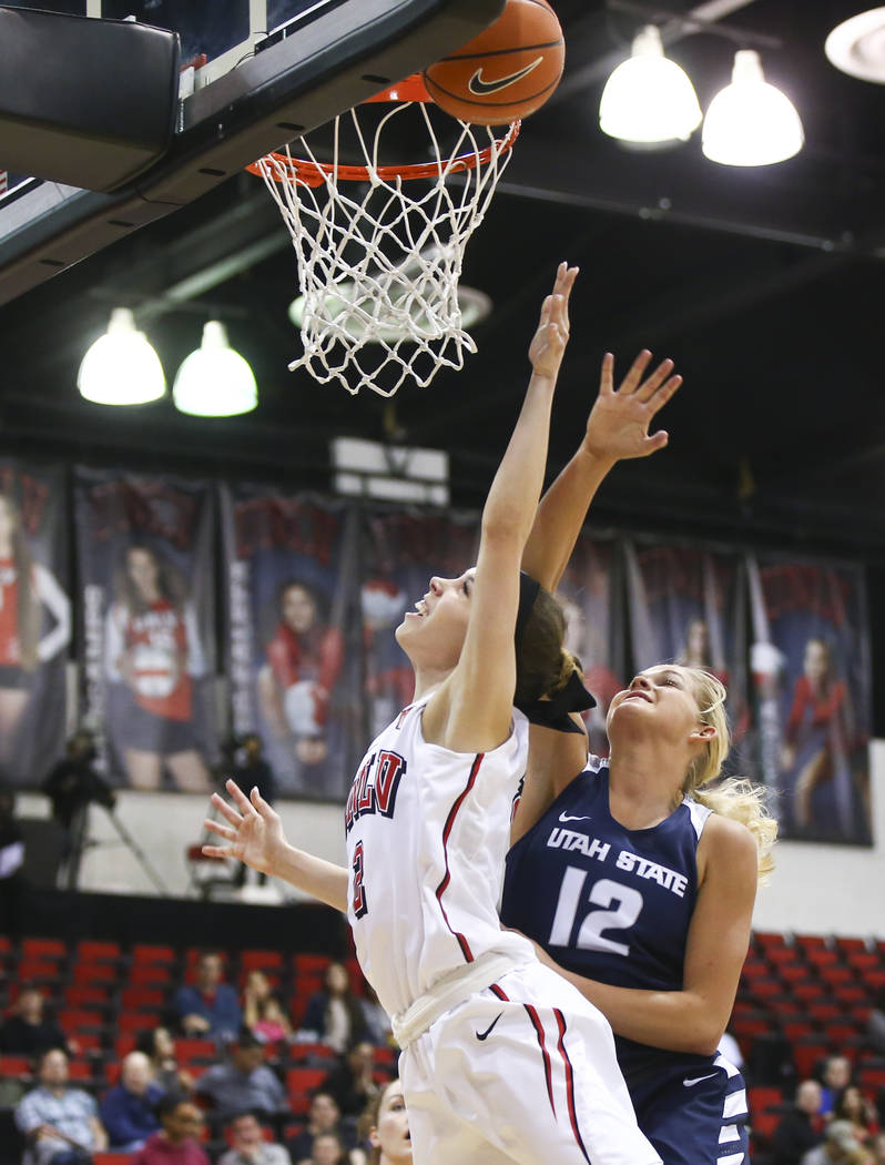 UNLV Lady Rebels guard Brooke Johnson (2) goes to the basket as Utah State Aggies guard/forward Hailey Bassett (12) defends during the first half of a basketball game at the Cox Pavilion in Las Ve ...