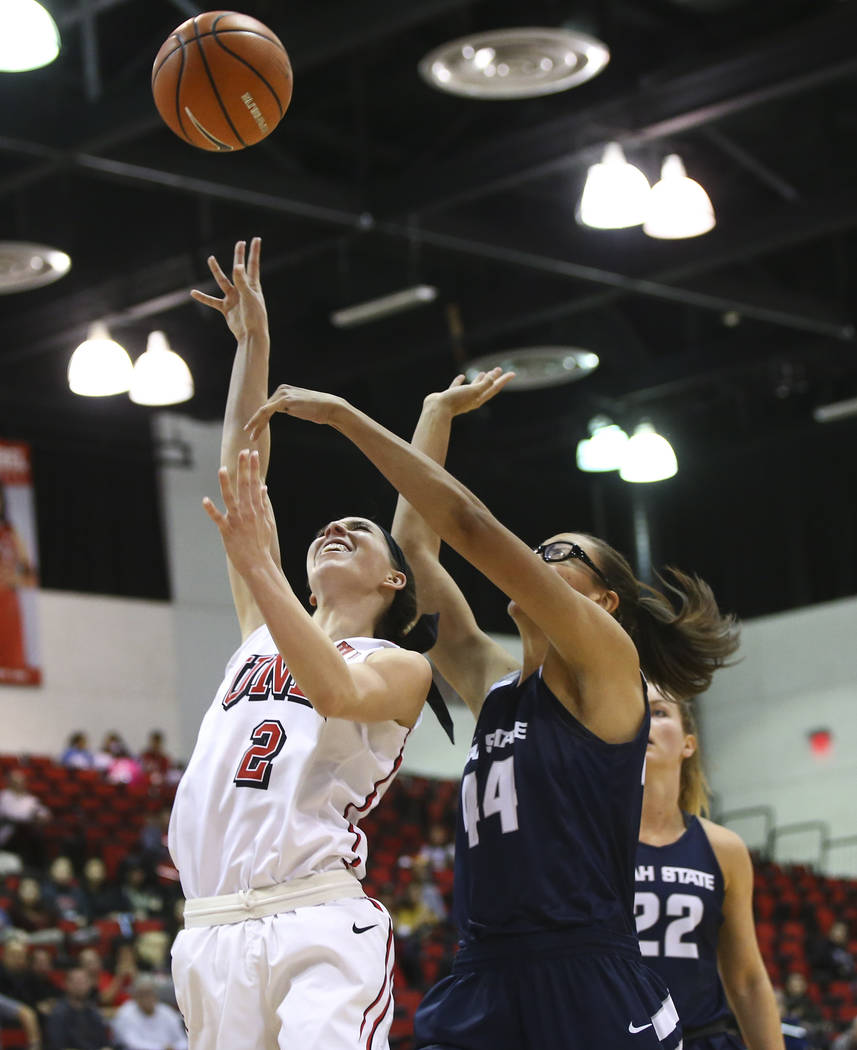 UNLV Lady Rebels guard Brooke Johnson (2) goes to the basket as Utah State Aggies center Deja Mason (44) defends during the second half of a basketball game at the Cox Pavilion in Las Vegas on Fri ...