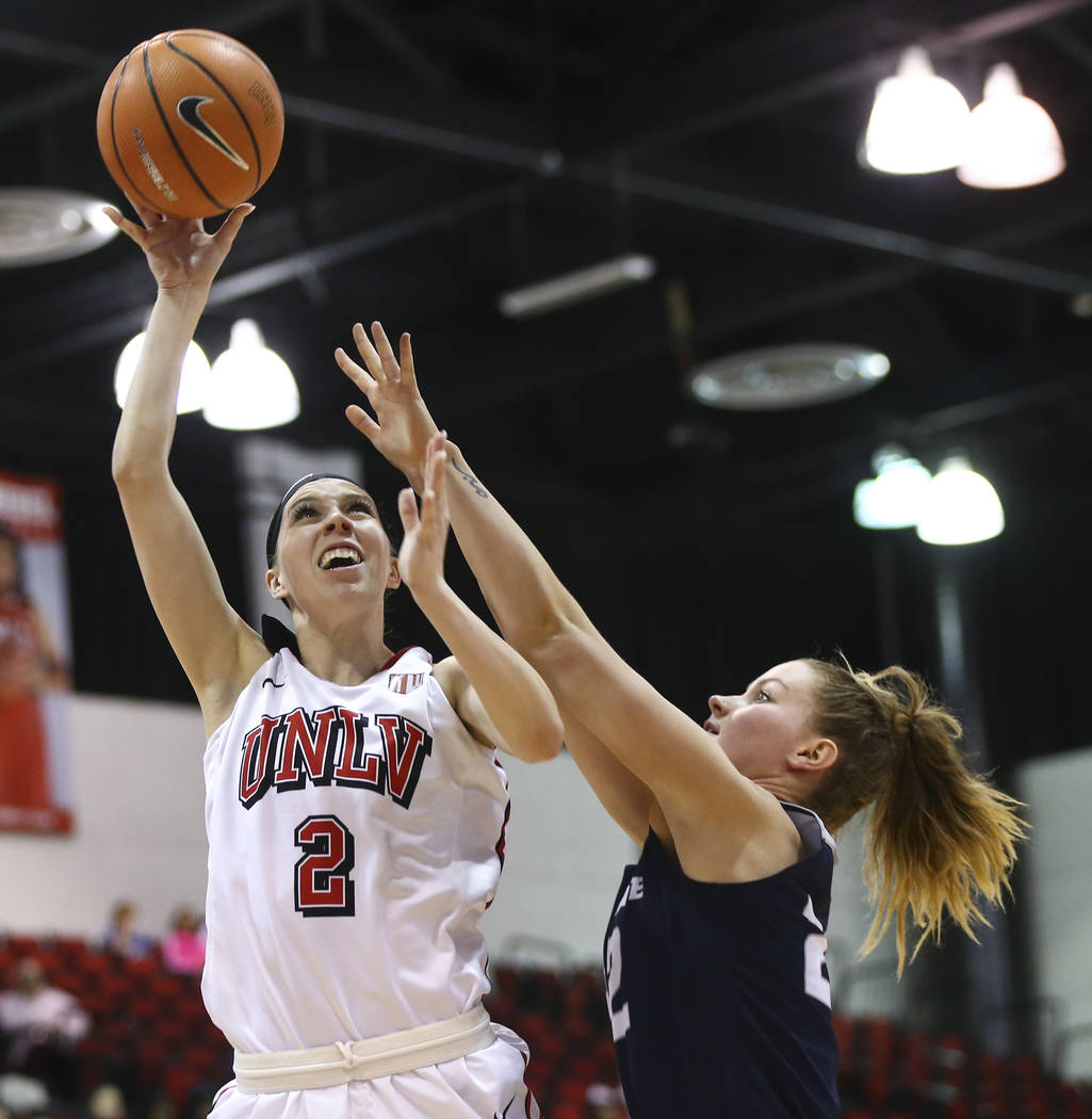 UNLV Lady Rebels guard Brooke Johnson (2) shoots as Utah State Aggies guard Rachel Brewster (22) defends during the second half of a basketball game at the Cox Pavilion in Las Vegas on Friday, Mar ...
