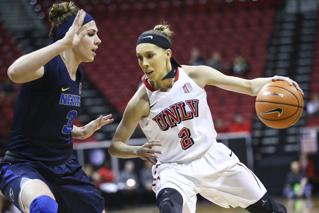 UNLV Lady Rebels guard Brooke Johnson (2) drives against UNR Wolf Pack forward Teige Zeller (3) during the first half of a basketball game in the Mountain West tournament quarterfinals at the Thom ...