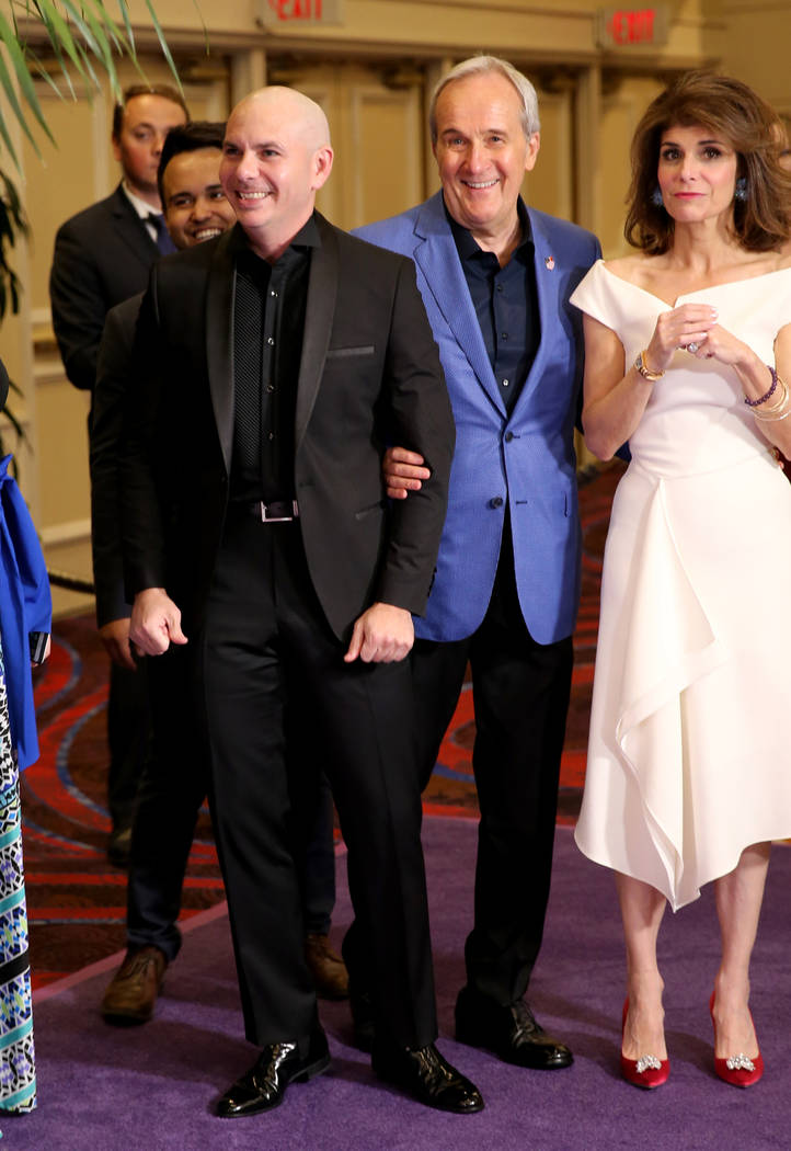 Planet Hollywood resident headliner Pitbull, left, prepares to walk the purple carpet with Larry and Camille Ruvo at the 22nd annual Power of Love gala in the MGM Grand Garden Arena in Las Vegas S ...