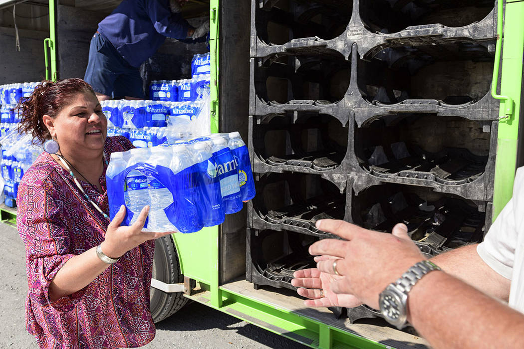 Yerington Paiute tribe chairman Laurie Thom helps offload water from a delivery truck on the outskirts of Yerington on Friday. (AP Photo/Scott Sady)