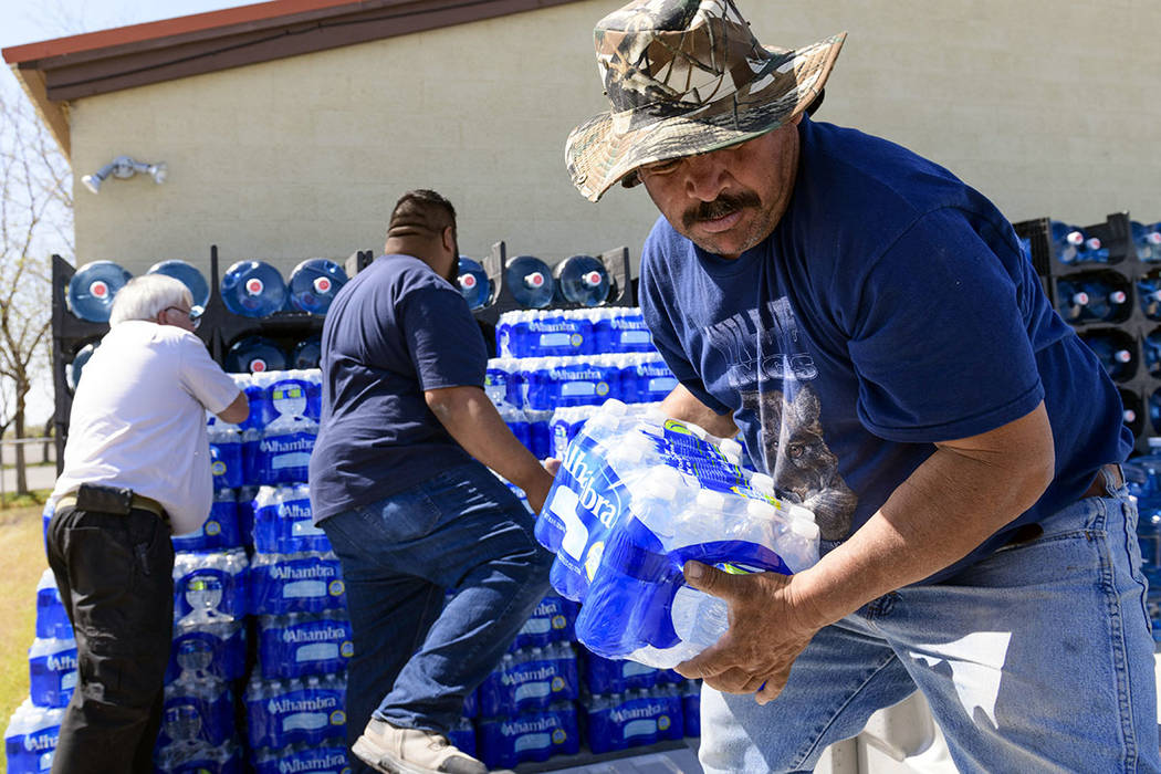 Nicolas Cuevas, right, and others load up plastic water bottles to distribute to members of the Yerington Paiute tribe after their weekly water delivery was left at the tribal border in Yerington ...