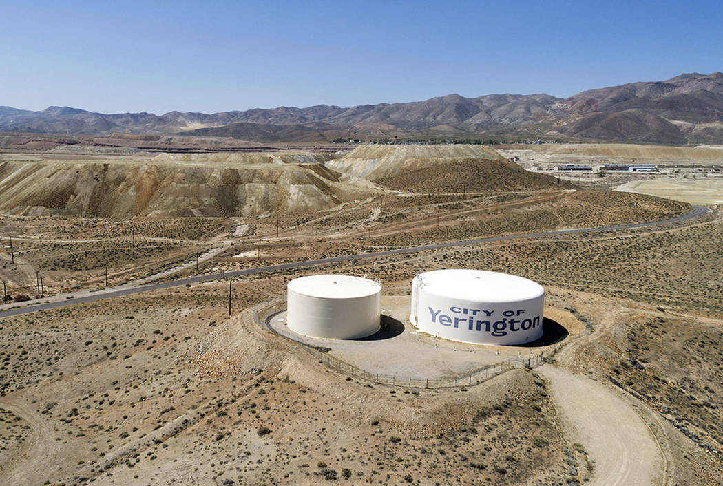 Water tanks for the town of Yerington, with the abandoned Anaconda mine pit, source of an underground plume of poisonous water in the background, are seen Friday. (AP Photo/Scott Sady)