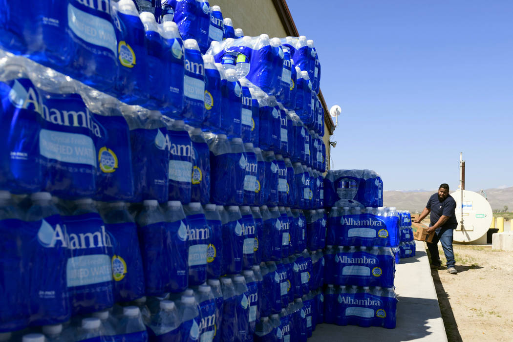 Tommy Gutierrez, a Paiute tribe member, helps load up some of the thousands of plastic water bottles that are distributed weekly to the Yerington Paiute tribe in Yerington on Friday. (AP Photo/Sc ...